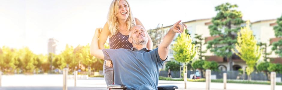 Mann im Rollstuhl geht mit einer Frau spazieren